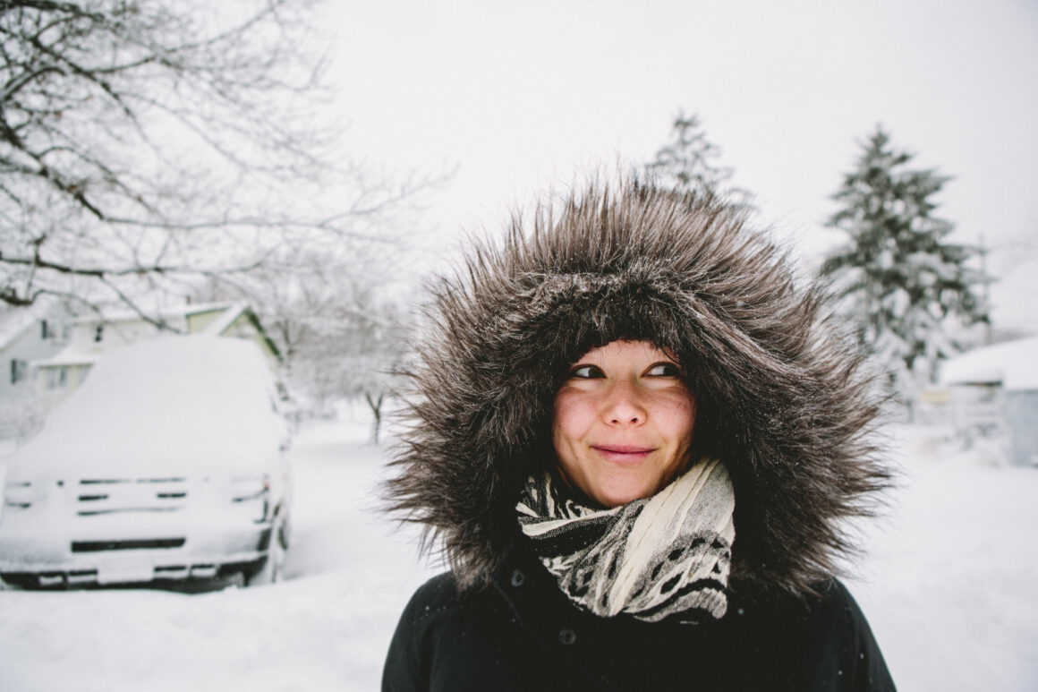 Woman in fur lined parka in snow.
