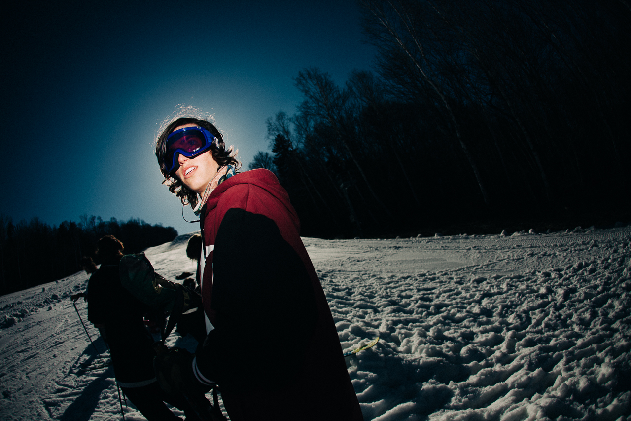 A skier walks to a feature at Mount Snow