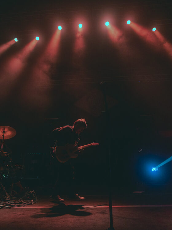 Musicians performing onstage on dark background